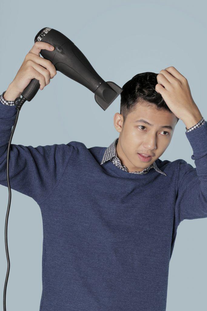 Asian man blow drying his short hair