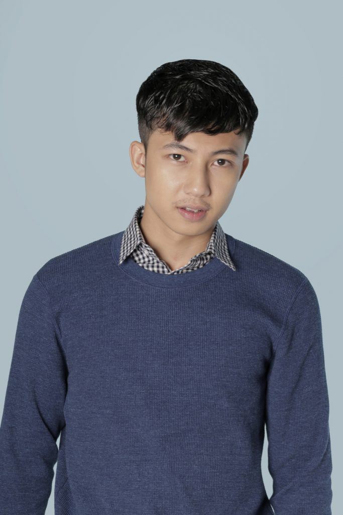 Asian man with short hair wearing a blue sweater