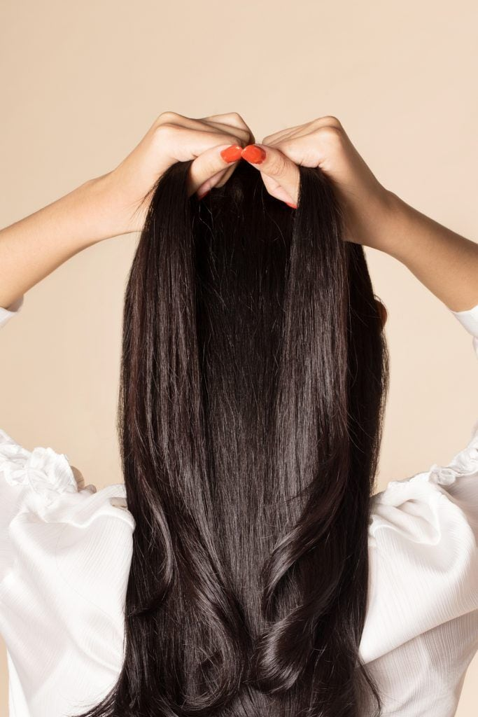 Back shot of an Asian woman diving a section of her hair into two parts
