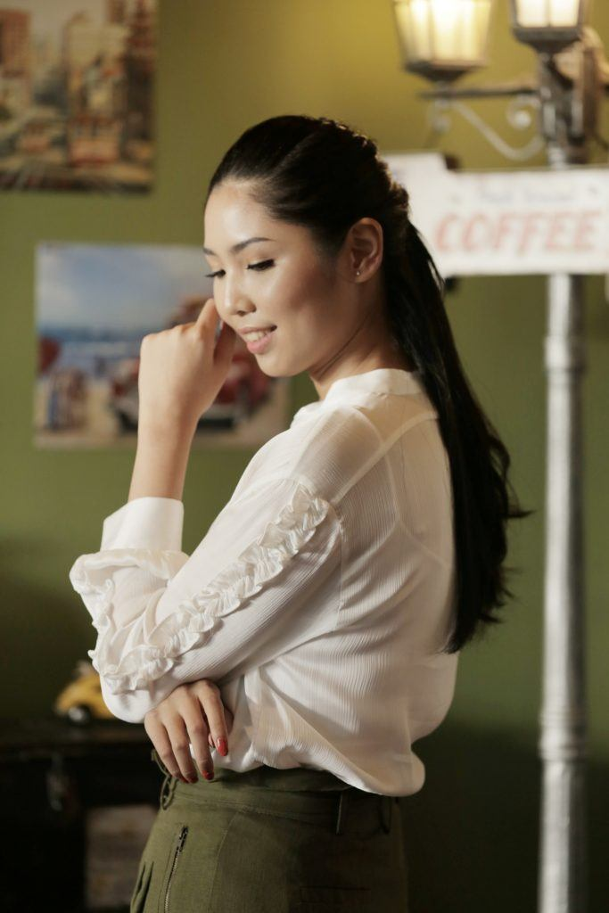 Asian woman with long hair in a half up Dutch infinity braid