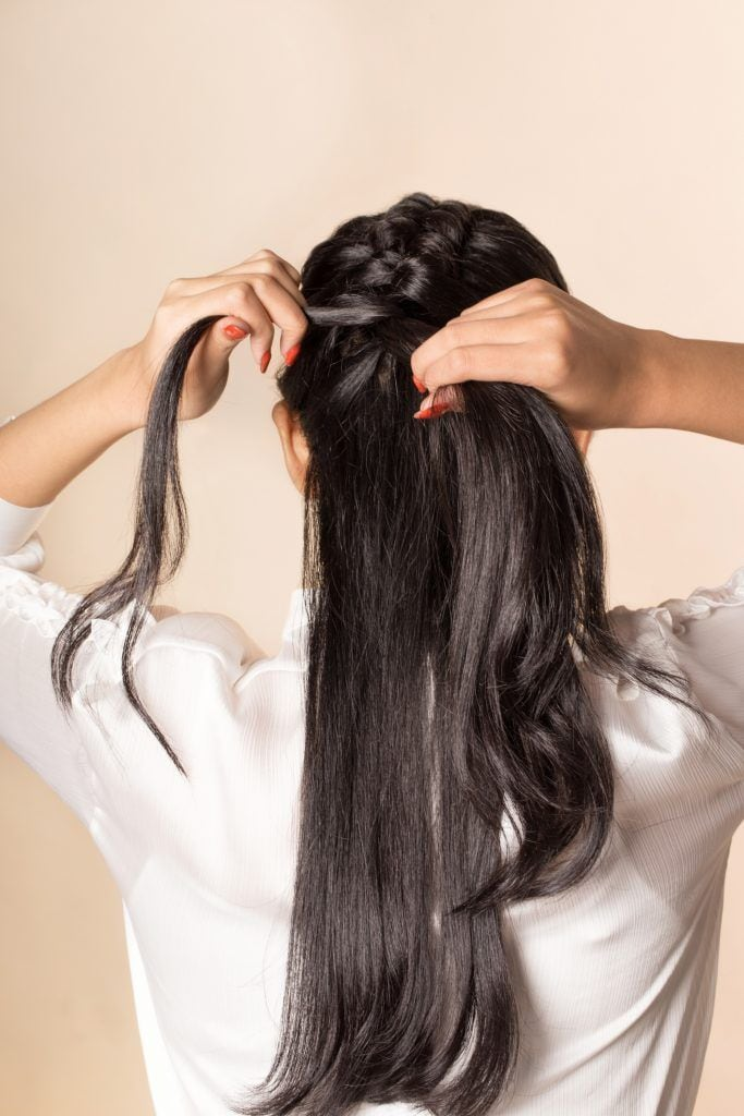 Back shot of an Asian woman finishing her hairstyle