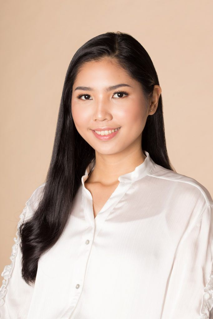 Asian woman with long black hair wearing a white polo