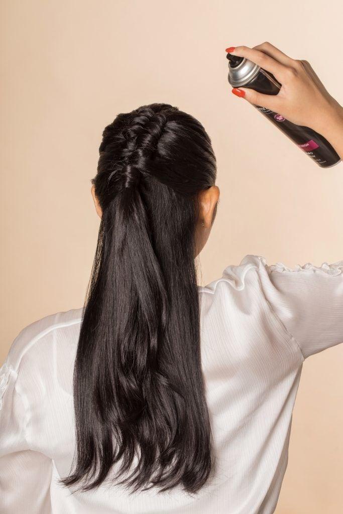Back shot of an Asian woman spraying hairspray on her hair
