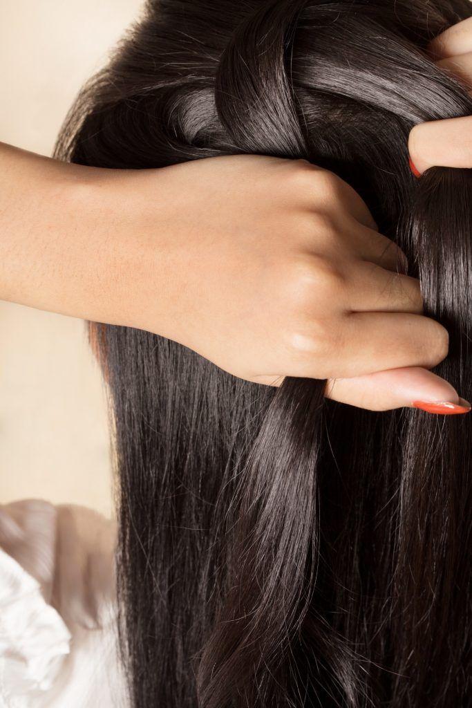 Closeup shot of an Asian woman looping her hair