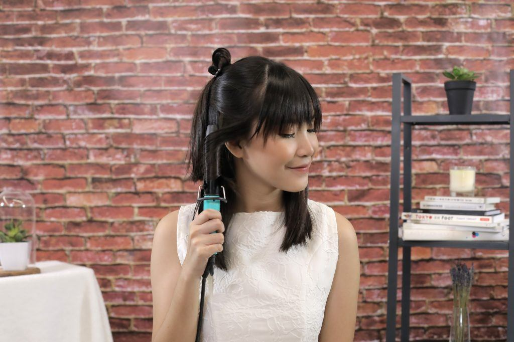 girl wearing a white top is curling her hair with a curling iron