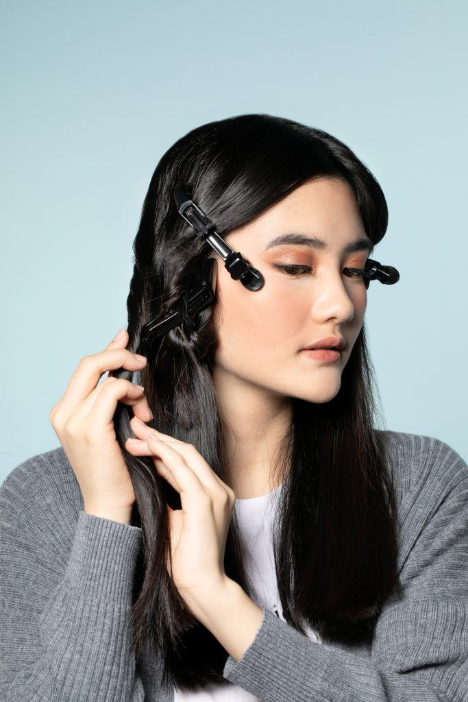 How to style curtain bangs: Asian woman twisting and clipping sections of her long hair