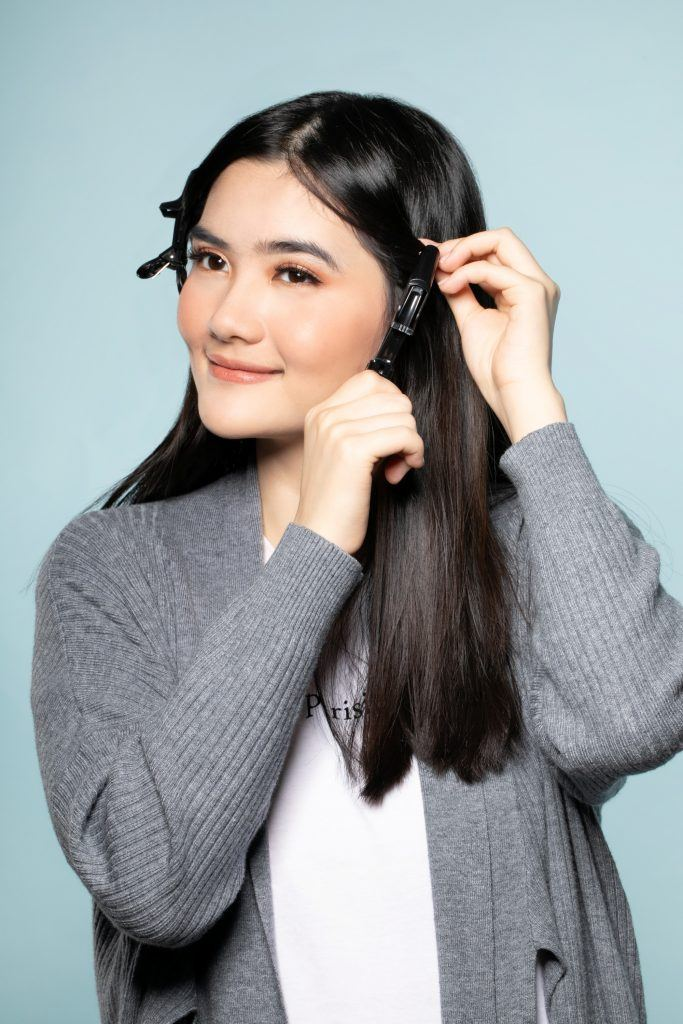 How to style curtain bangs: Asian woman clipping portions of her long hair
