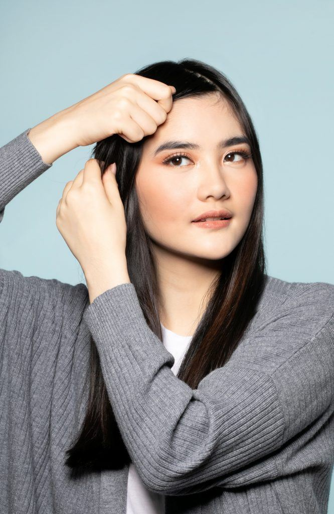 Asian woman applying hair product on her bangs