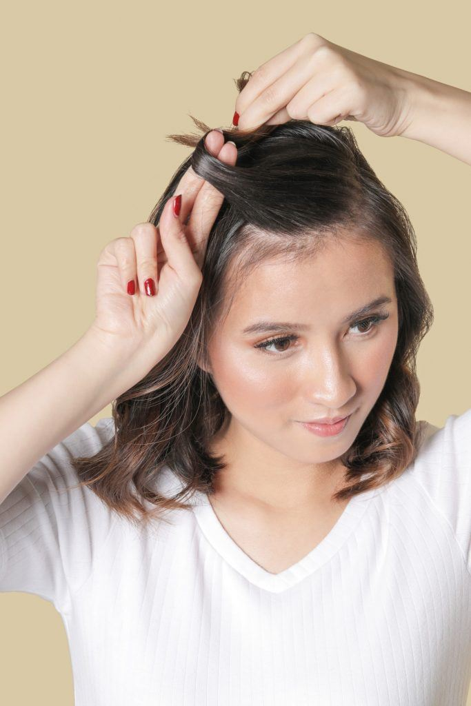 Asian girl with a white top is making a small knot with her hair for her Triple Knot Accent for Medium hair style