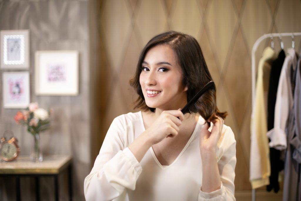Asian woman combing her hair to create a wavy bob with deep side part