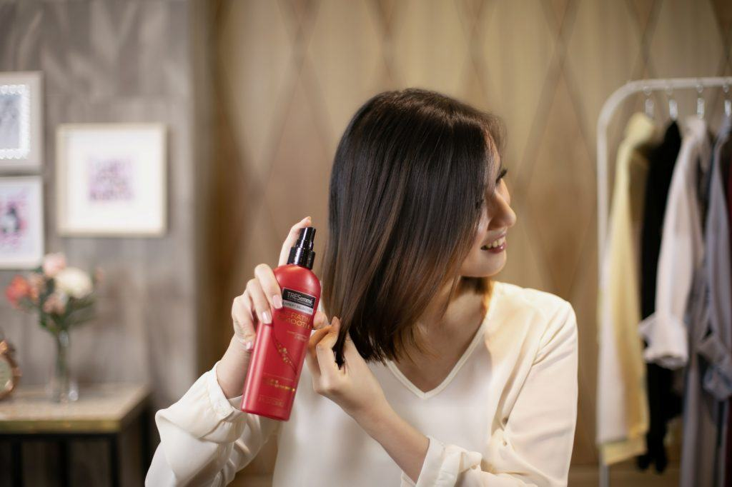 Asian woman spraying heat protectant on her bob