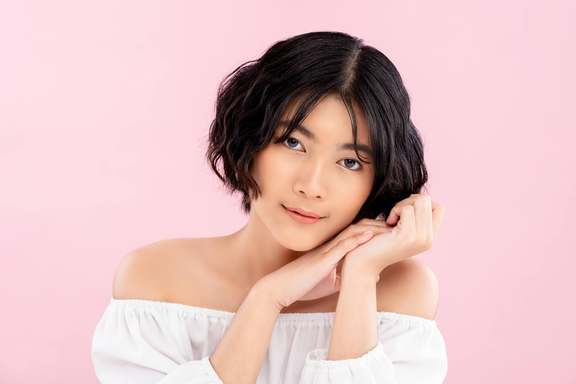 Asian woman with short wavy hair wearing a white off-shoulder top