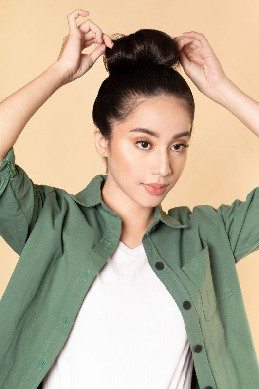 Asian woman loosening strands in her big top knot