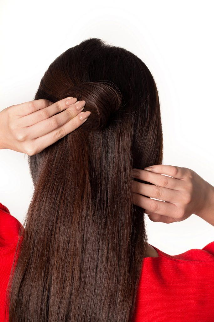Back shot of Asian woman styling her long dark hair