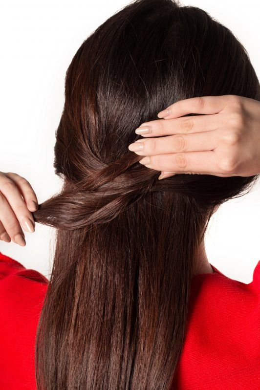 Back shot of an Asian woman styling her long dark hair