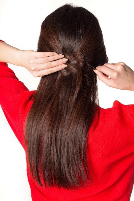 Back shot of an Asian woman pinning her Celtic knot half updo