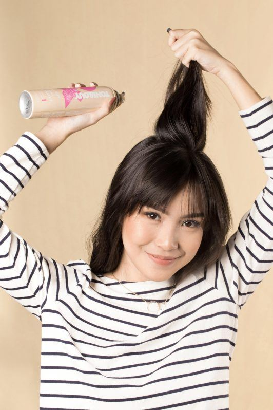 Asian woman spraying on her hair