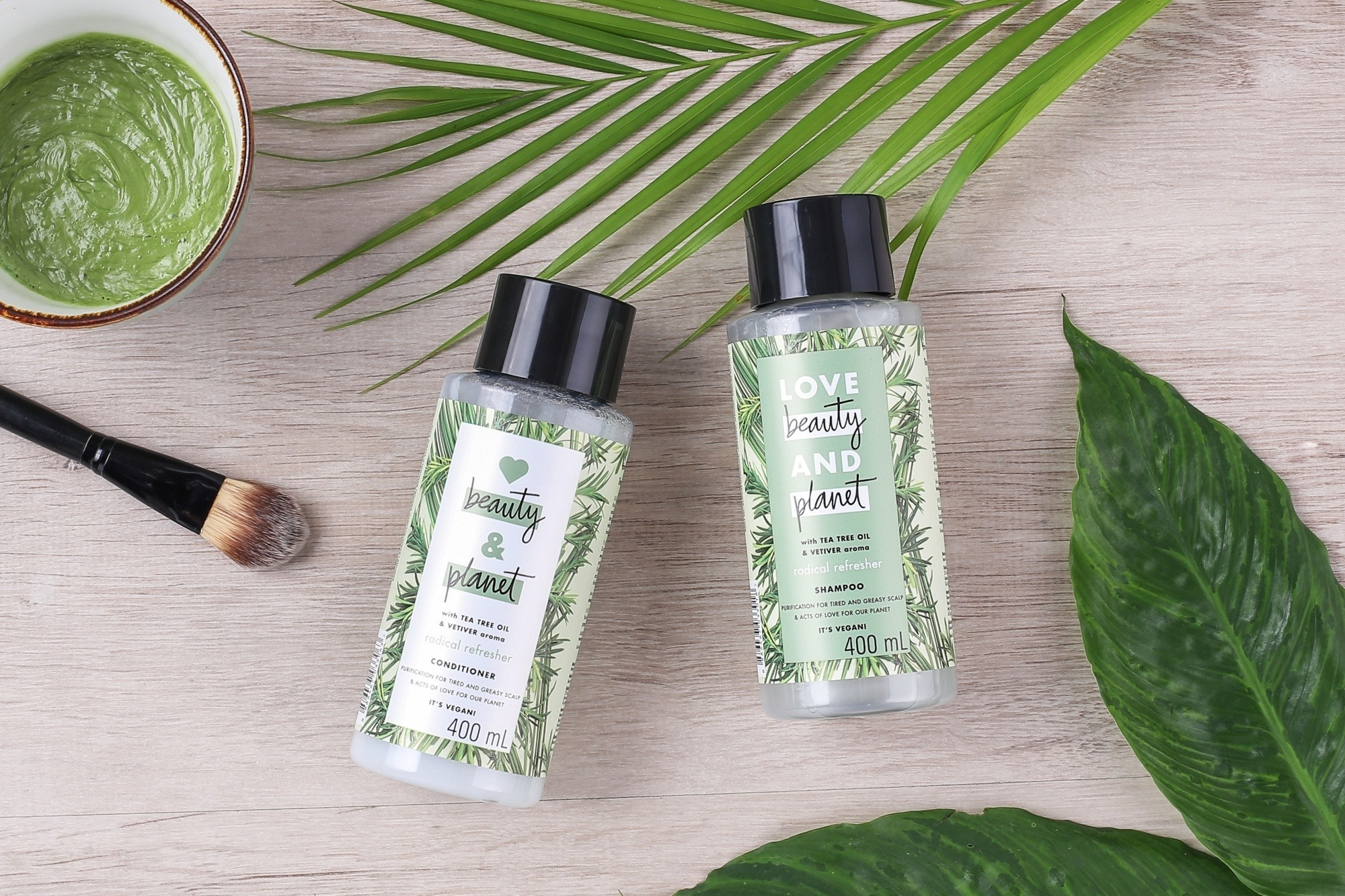 Eco-friendly hair products: Flatlay of shampoo and conditioner with leaves
