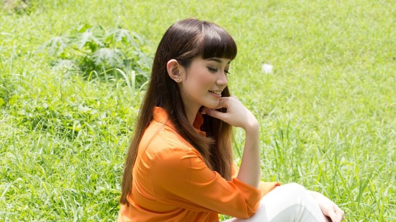 Eco-friendly hair products: Asian woman with long dark hair sitting on the grass
