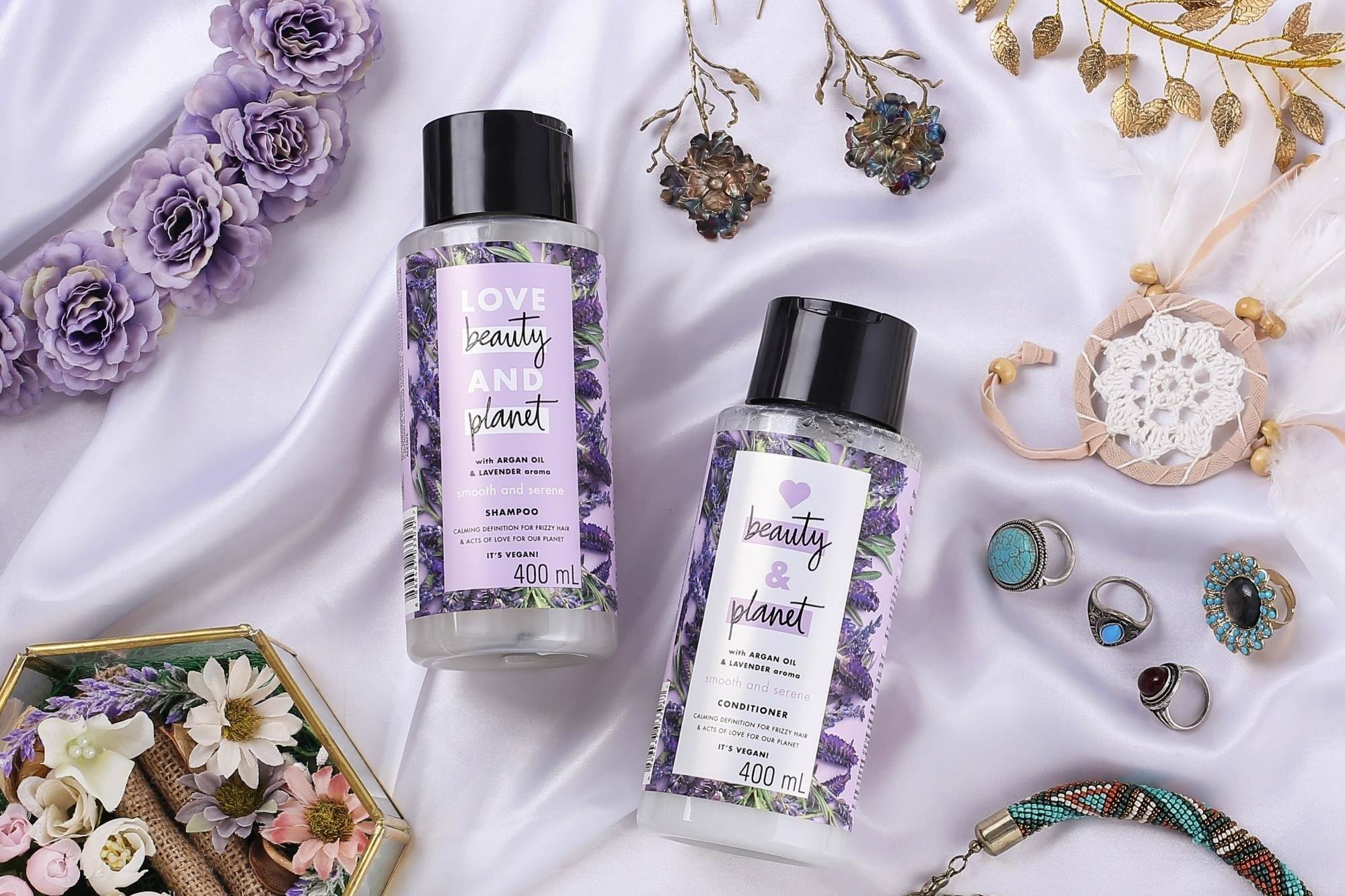 Eco-friendly hair products: Flatlay of shampoo and conditioner with faux flowers and accessories