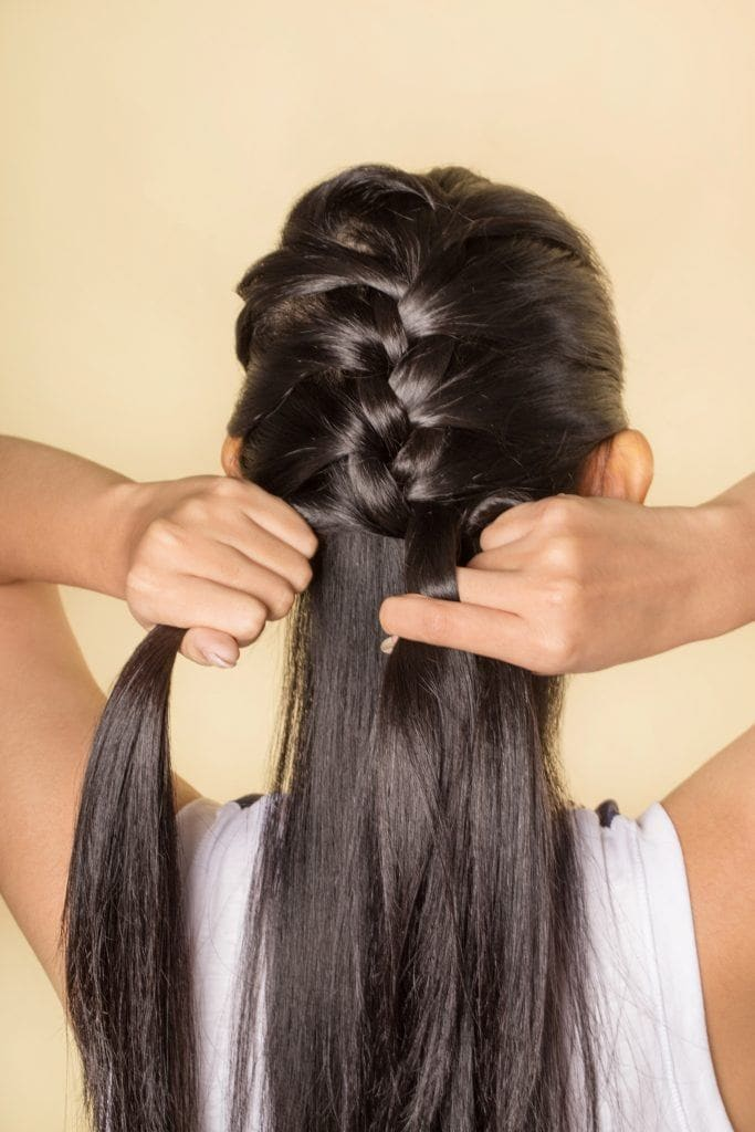 Back shot of an Asian woman creating a French braid on her long black hair