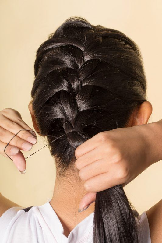 Back shot of an Asian woman finishing her French braid