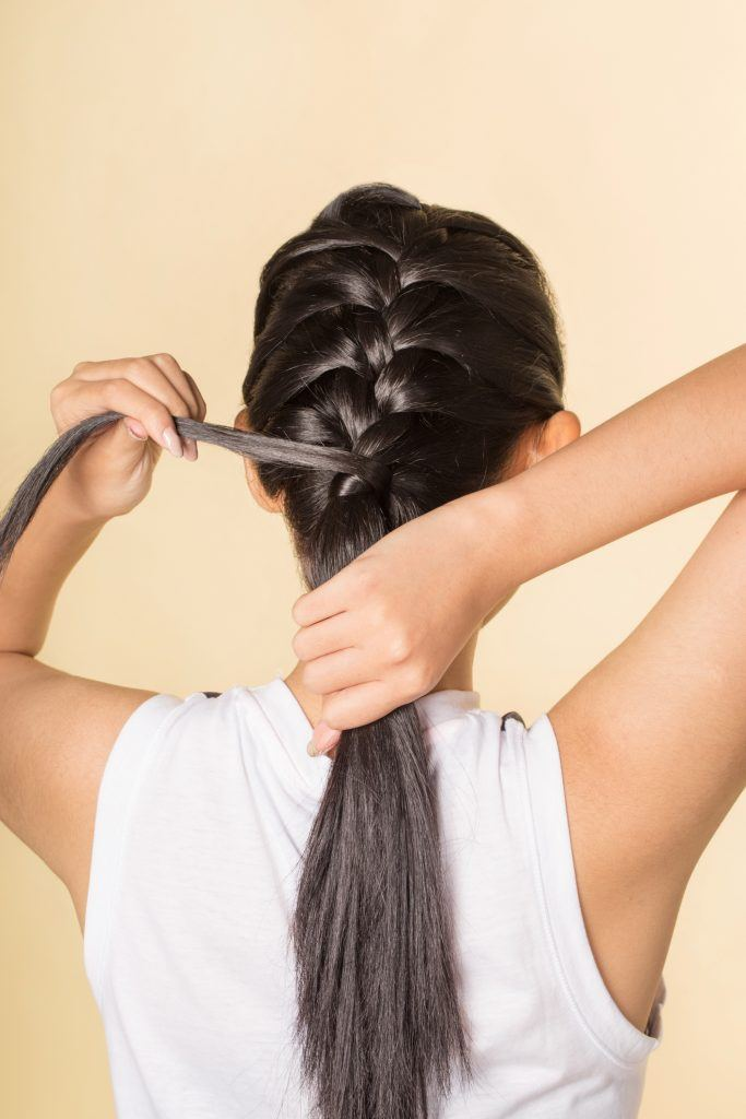 Back shot of an Asian woman wrapping a section of hair around the end of her French braid