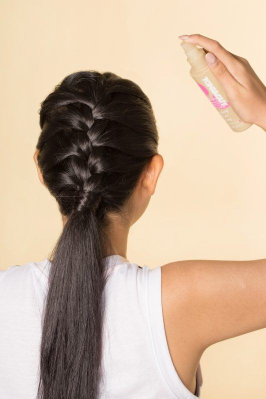 Back shot of an Asian woman spraying shine spray on her French braid hairstyle