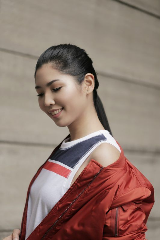 Asian woman with long hair in french braid into sleek ponytail wearing a sleeveless top and red jacket