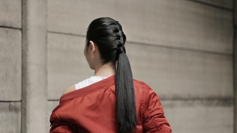 Back shot of an Asian woman with long hair in French braid into sleek ponytail wearing a red jacket