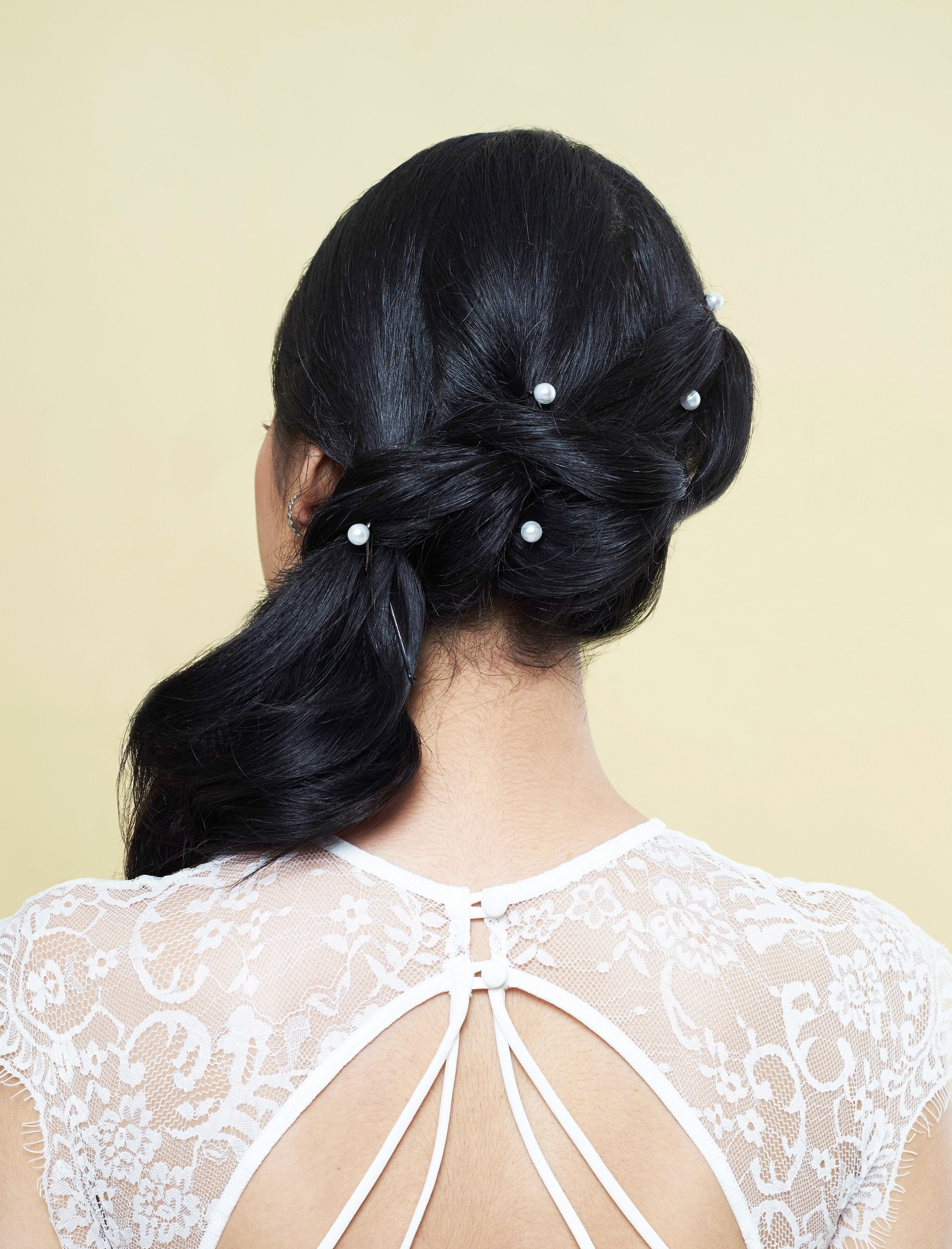 Graduation hairstyles: Back shot of an Asian woman with black hair in pony braid