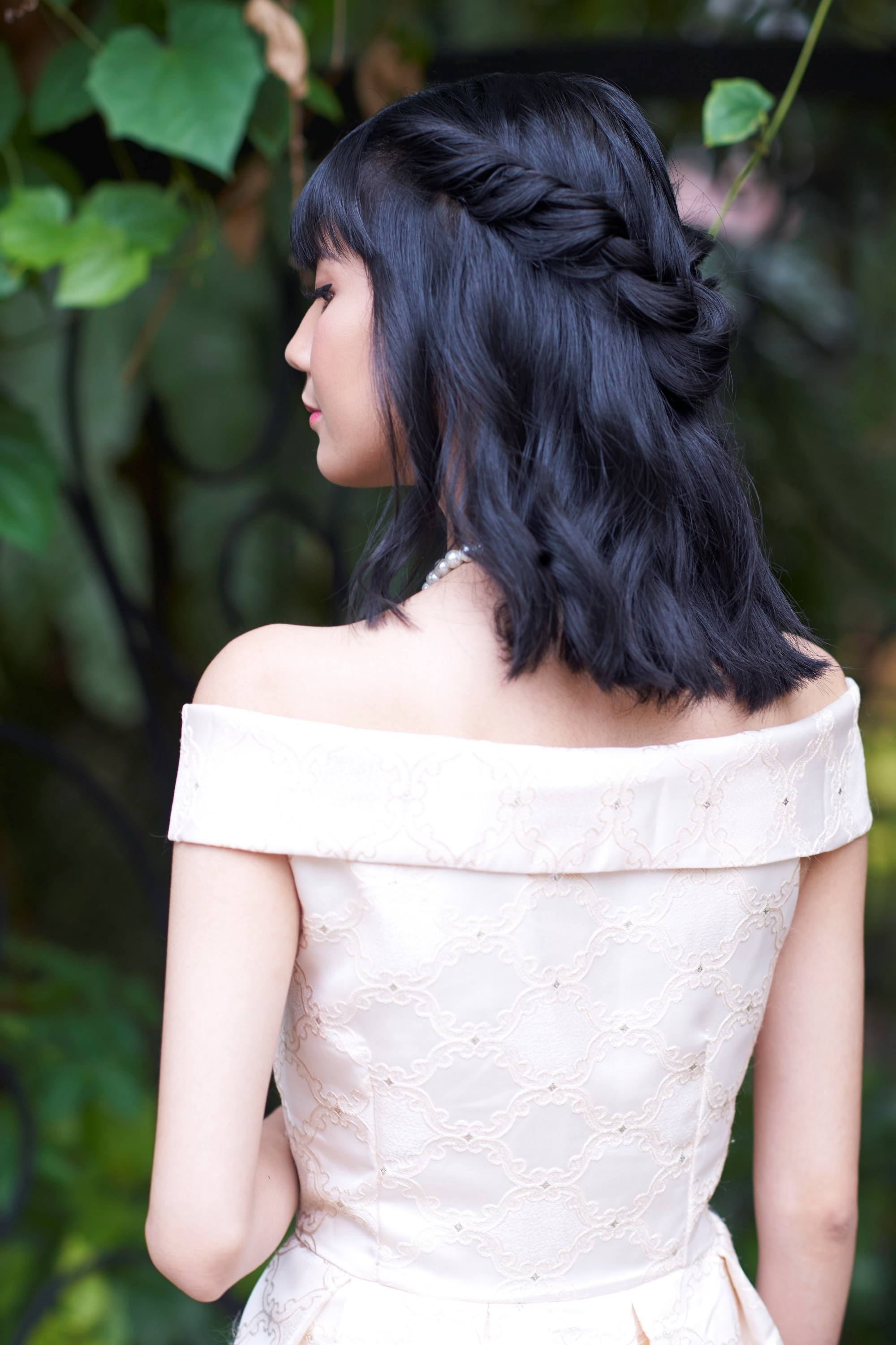 Graduation hairstyles: Back shot of an Asian woman with twisted crown braid half updo