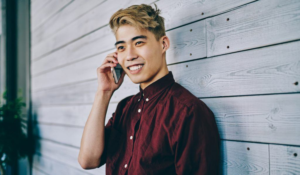 Asian man with blonde hair color for men wearing a maroon polo