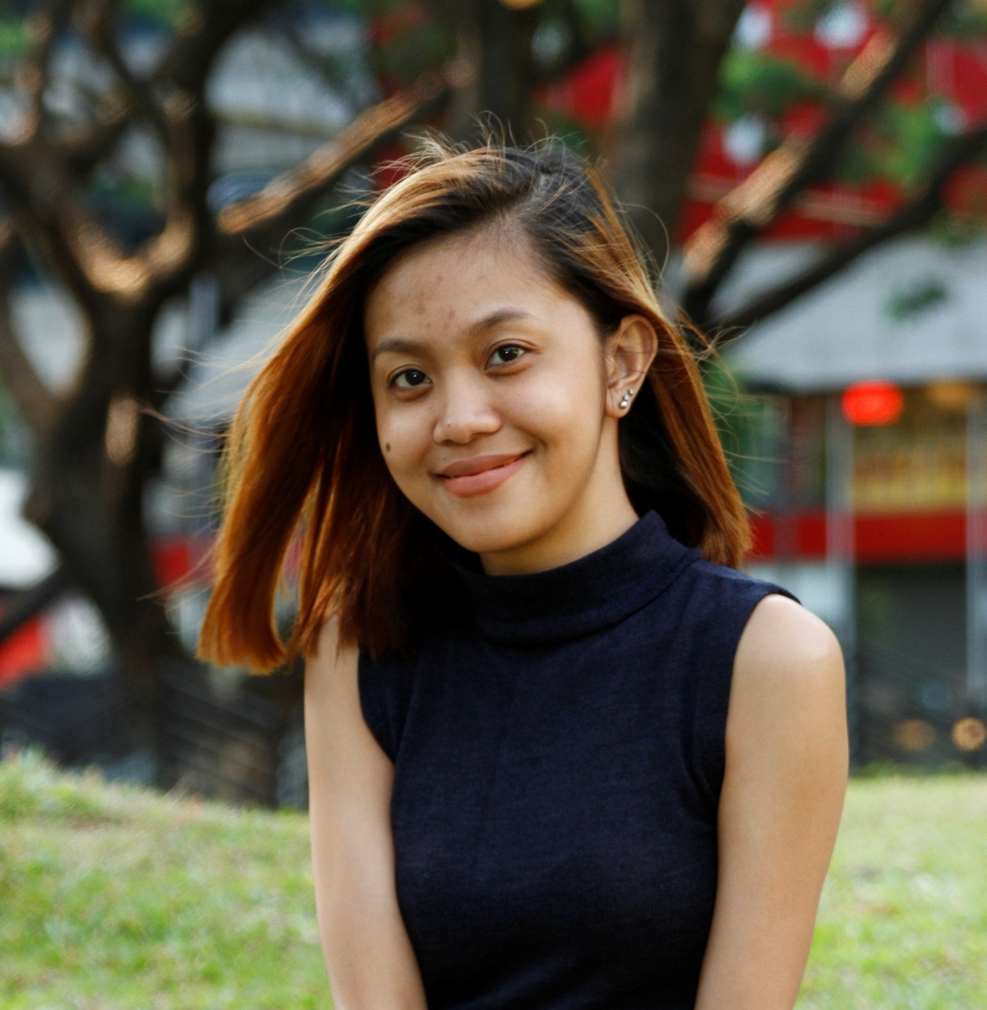 Filipina with shoulder-length dark brown hair smiling in a park