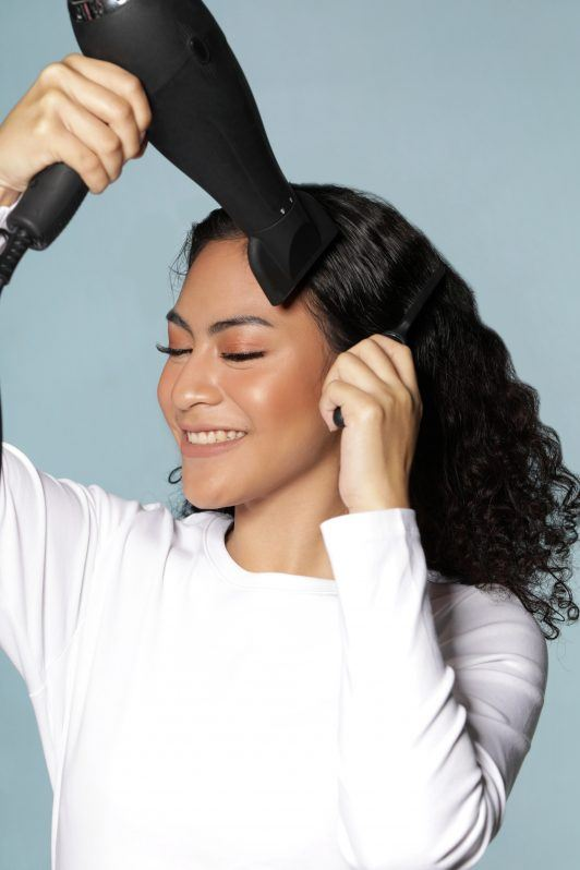 Asian woman blowdrying her dark curls and smiling