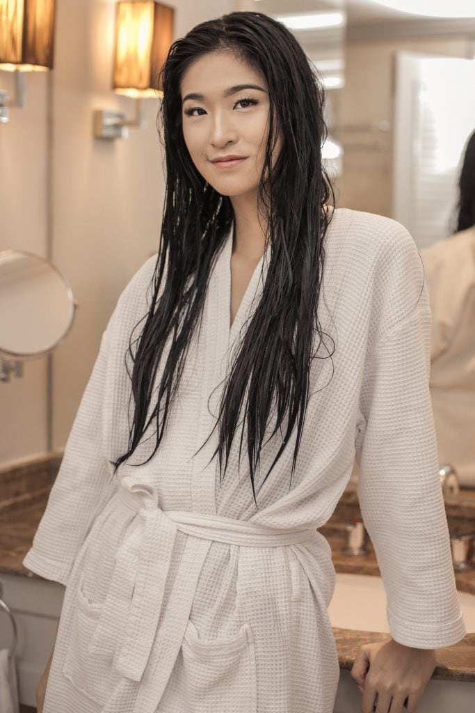 Asian woman with long wet black tresses wearing a white robe