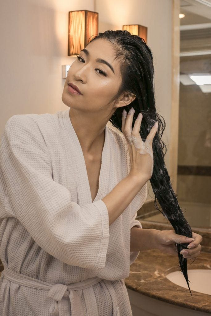 Asian woman putting conditioner on her long black wet locks and wearing a white robe