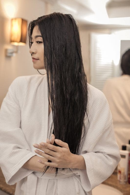 Asian woman with long black hair wearing a white robe
