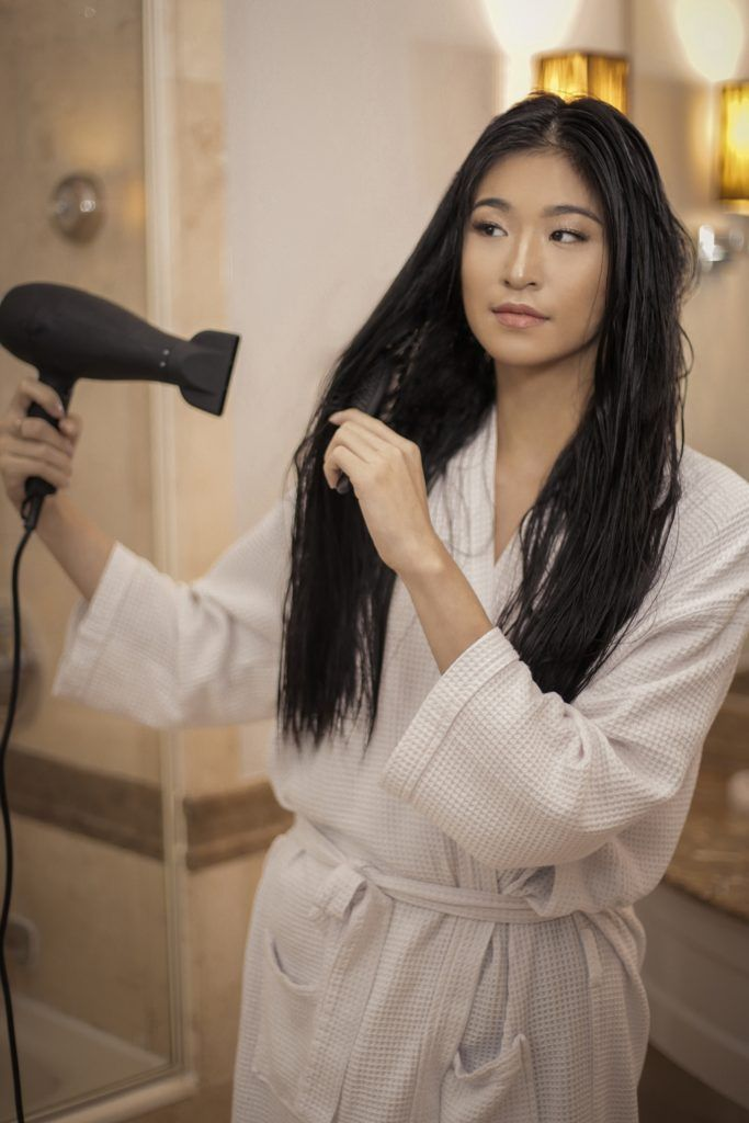 Asian woman blow drying her long black hair in the bathroom