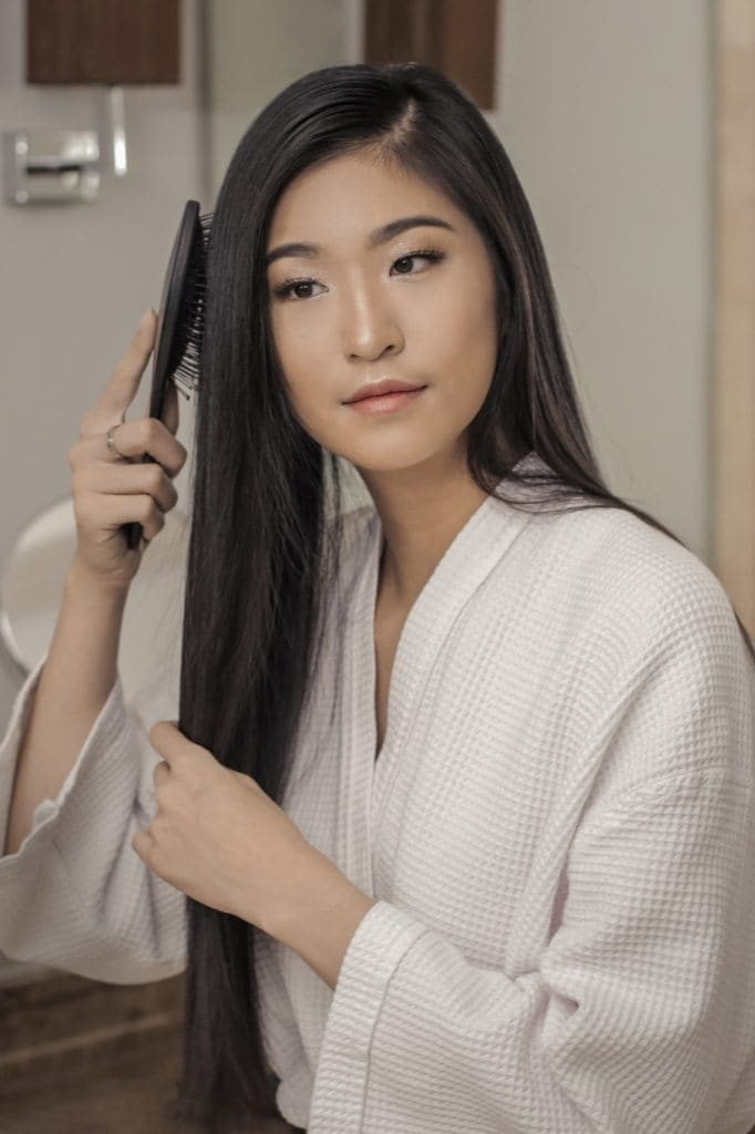 Asian woman wearing a white robe brushing her long straight hair