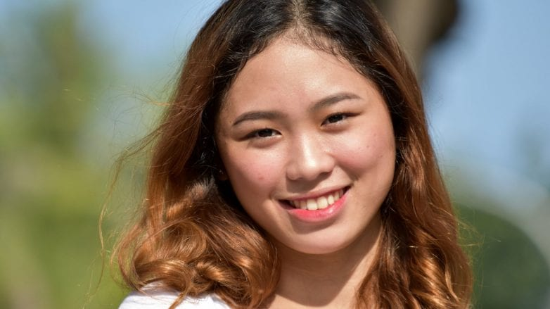 Asian woman with light brown ombre hair smiling