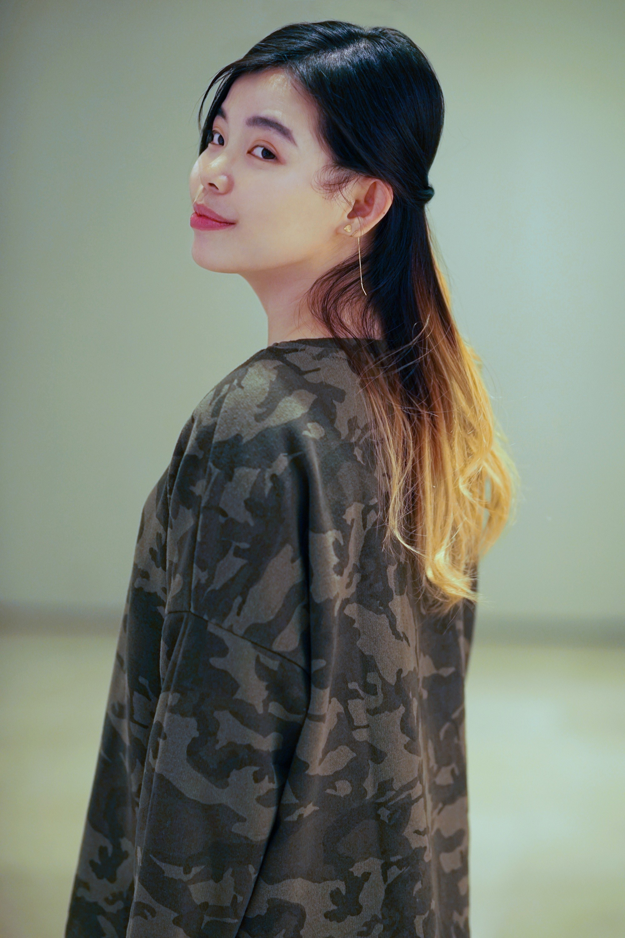Asian woman with long light brown ombre hair