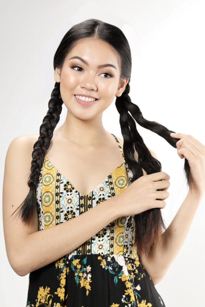 Asian woman unraveling her braids smiling
