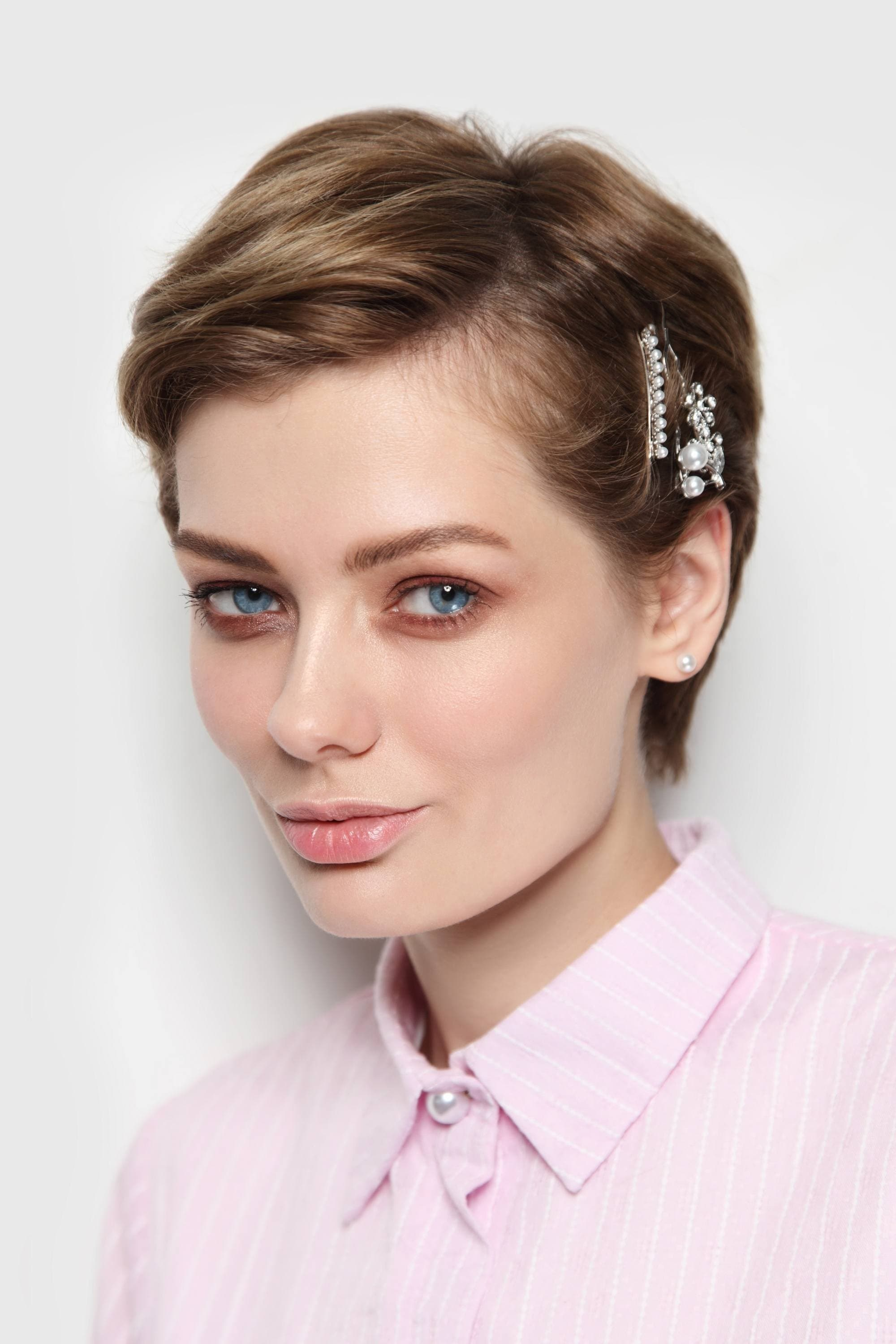 Woman with brown pixie cut with hair clips