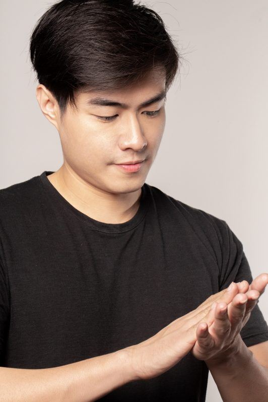 Asian man rubbing his palms together