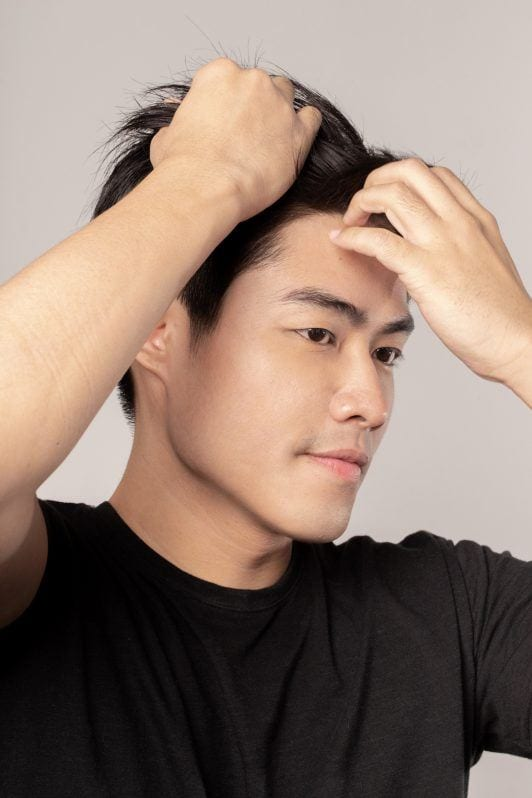 Asian man styling his hair to create modern quiff for men