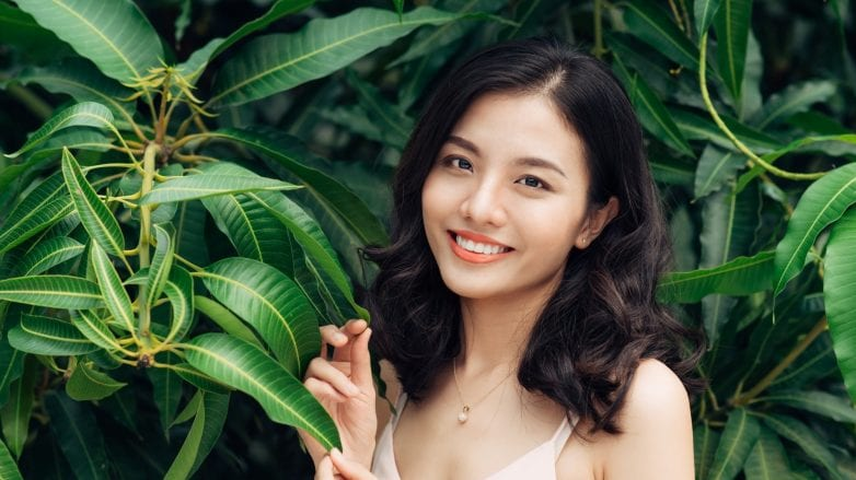 Naturals range discounts: Asian woman with dark wavy hair smiling with leaves in the background