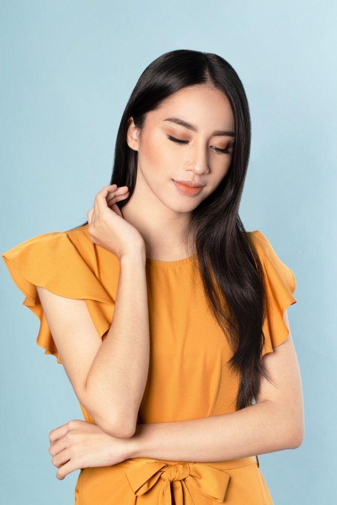 V-Shape haircut: Asian woman prepping her hair for Sleek braid with accessories