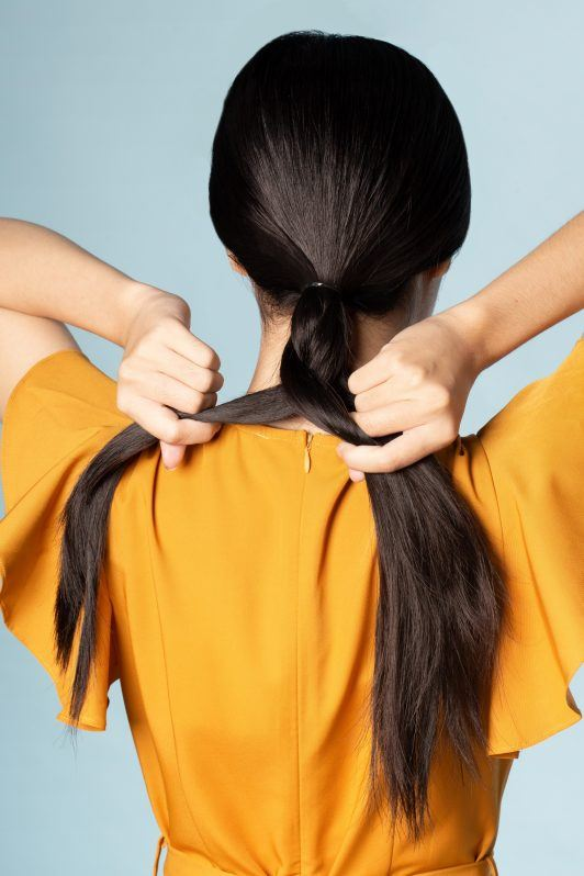 Asian woman braiding her long black hair