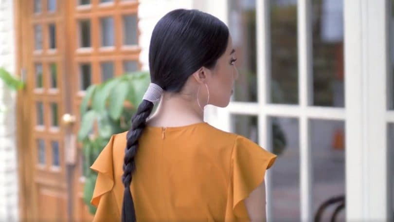 Asian woman with hair in sleek braid with accessories